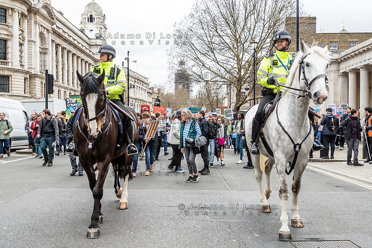 London, England on 15 March 2019: the protesters students move on the street escorted by police on horseback during the youth climate strike in London. The protest against climate change and urge the government to take action.The global movement has been inspired by teenage activist Greta Thunberg, who has been skipping school every Friday since August to protest outside the Swedish parliament. Photo Adamo Di Loreto/BunaVista*photo