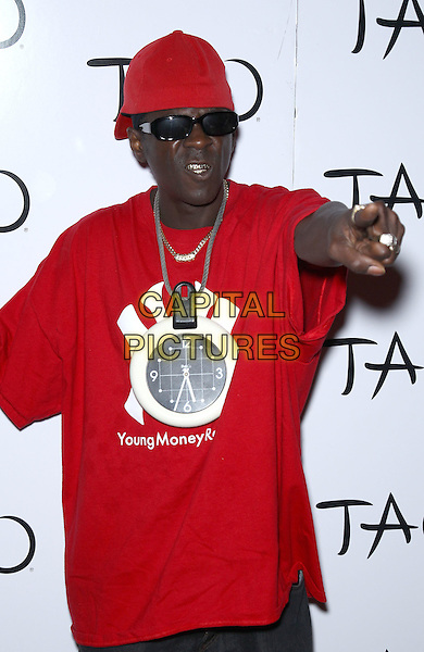 Public Enemy - Flavor FLav.Worship Thursday with Public Enemy at Tao Nightclub inside The Venetian Las Vegas, NV, - Las Vegas, Nevada, USA..August 18th, 2011.group half length red t-shirt red baseball cap hat sunglasses shades young money records necklace hand arm teeth.CAP/ADM/MJT.© MJT/AdMedia/Capital Pictures.