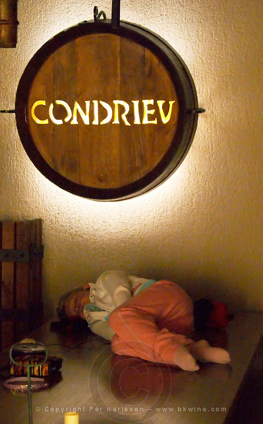 A sign on the wall makde from an old oak barrel with carved thext Condrieu that is lit by a lamp. On a table below, a young girl that is sleeping and who thinks it is boring with wine tastings.  Condrieu, Rhone, France, Europe  Domaine Georges Vernay