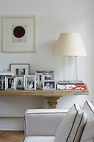 A contrasting rustic side table in the living room is laden with family photographs