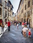 Tourists walk in a shady street of San Gimignano, Siena-Tuscano, Italy