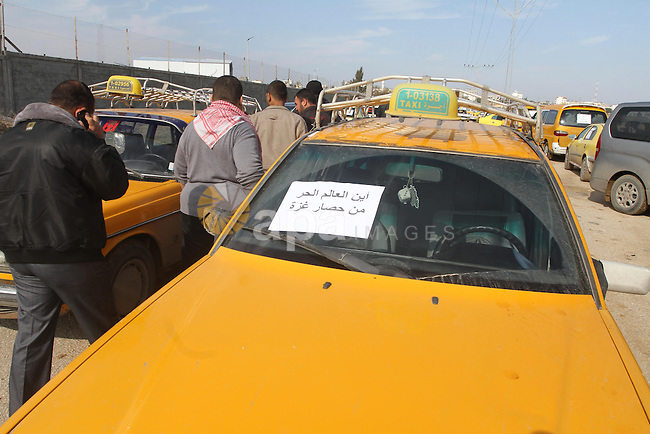 Palestinian taxi drivers stop their cars during a protest to solve the crisis of fuel, in front of the Karni crossing in the eastern Gaza city, on Jan. 01, 2014. Photo by Mohammed Asad