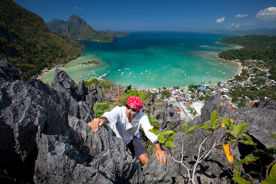 A man rock climbs on top of sharp limestone spires overlooking the village of El Nido and the Bacuit Archipelago in Palawan, Philippines.
