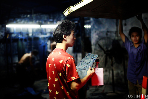 "A manager checks a jeans sample in Mr Huang's factory in Zhongshan city, China.  .This picture is part of a photo and text story on blue jeans production in China by Justin Jin. .China, the ""factory of the world"", is now also the major producer for blue jeans. To meet production demand, thousands of workers sweat through the night scrubbing, spraying and tearing trousers to create their rugged look. .At dawn, workers bundle the garment off to another factory for packaging and shipping around the world..The workers are among the 200 million migrant labourers criss-crossing China.looking for a better life, at the same time building their country into a.mighty industrial power."