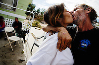 "Niland, California, February 23, 2008 - Recent newlywed Jerry Jones kisses his new wife Darla at the slab of Johnny Hilliard. The couple, which found a common bond through their mutual addition to crystal meth and crack cocaine, says that they are meant for each other. Just prior to meeting Jerry, a local drug dealer kidnapped Darla and, she says, ""I was anally raped for two weeks before I escaped."" Jerry found her walking down the road after her kidnapping and now sees himself as her protector. He added, ""I am here to protect her and take care of her. She is my woman now.""."