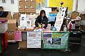 "Minamisanriku, Miyagi, Japan - A woman sells souvenirs and charity  products at Minamisanriku Volunteer Center, one year after the tsunami. The Latin group of volunteers ""Todos con Japon"" visits Miyagi area during this Golden Week."