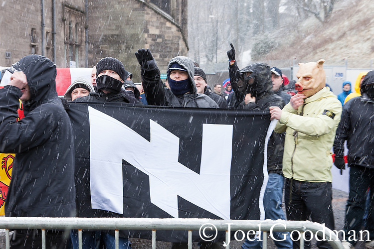 © Joel Goodman - 07973 332324 . 04/02/2012 . Rochdale , UK . Protesters carrying a flag bearing a Wolfsangel , a symbol used by the Nazi 2nd SS Panzer Division during the 2nd World War . The North West Infidels , a Nationalist group splintered from the EDL , protest outside Rochdale Town Hall . Protesters shout nationalist, Islamophobic and anti-Zionist slogans . Photo credit : Joel Goodman