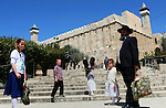 Israeli Jews walk outside the Tomb of the Patriarchs during the Jewish Passover holiday, in the West Bank city of Hebron, April 5, 2015. Due to the haste with which the Jews left Egypt some 3,500 years ago, the bread they had prepared for the journey did not have time to rise, therefore to commemorate their ancestors' plight, religious Jews do not eat leavened food products throughout the eight-day Pesach holiday. Photo by Mamoun Wazwaz