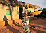 As the sun sets near Kangawa, in northern Malawi, Fryness Sambo, age 72, winnows the chaff from her corn.