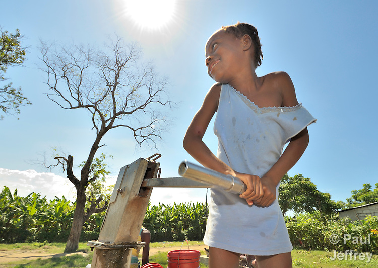 A girl gets water by pumping a well in the Haitian village of Vaudreuil.