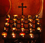Cross and votive candles in the mission chapel, San Juan Bautista, Calif.