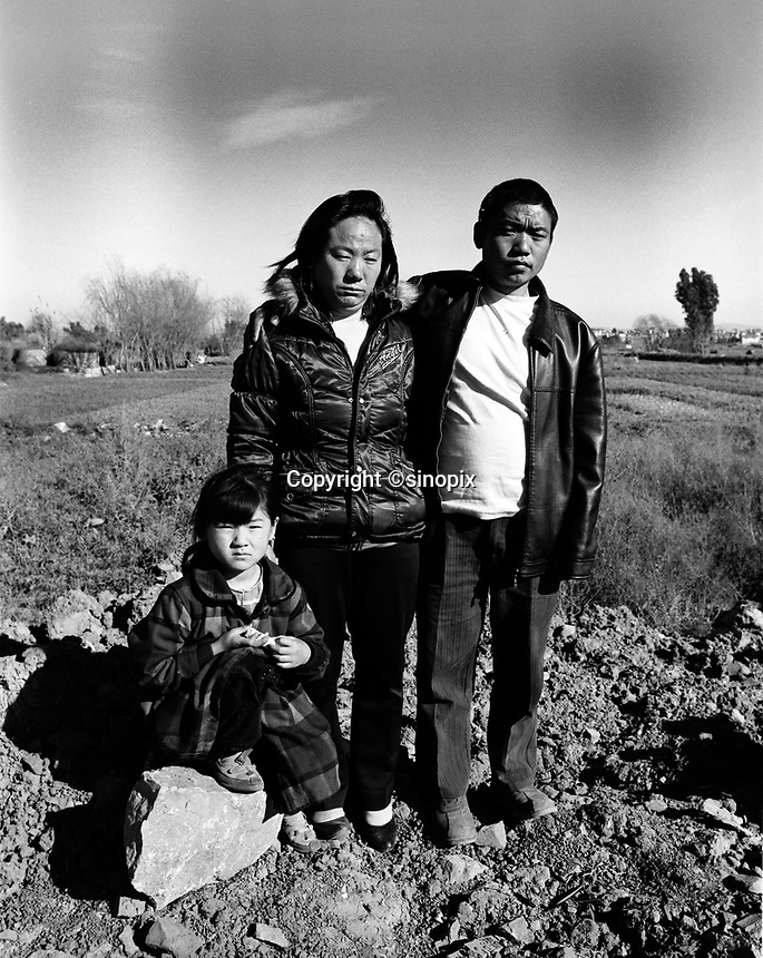 Mr Huang He, poses with his wife and and his daughter, one of their three children, on the suberbs of Kunming. Both parenst were sterilized by force in their remote farming village in Guizhou, Huang He says he did not receive an anaesthetic.<br /> 24 Nov 2007<br /> <br /> photo by Richard Jones / Sinopix