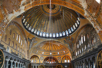 High angle view of interior showing Islamic elements in the ceiling, Hagia Sophia, 532-37, by Isidore of Miletus and Anthemius of Tralles, Istanbul, Turkey. Hagia Sophia, The Church of the Holy Wisdom, has been a  Byzantine church and an Ottoman mosque and is now a museum. The current building, the third on the site, commissioned by Emperor Justinian I, is a very fine example of Byzantine architecture. The historical areas of the city were declared a UNESCO World Heritage Site in 1985. Picture by Manuel Cohen.