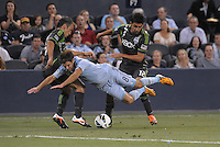 Graham Zusi (8) midfield Sporting KC gets knocked over by Sounders defenders..Sporting Kansas City defeated Seattle Sounders on penalty kicks, after a 1-1 tied game to win the Lamar Hunt Open Cup at LIVESTRONG Sporting Park, Kansas City, Kansas..