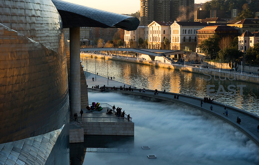 Visitors admire a mist-producing art installation in front of Guggenheim Museum in Bilbao, Spain, on December 27, 2011. The Guggenheim Museum Bilbao is a museum of modern and contemporary art, designed by architect Frank Gehry, covered by reflective titanium panels resembling fish scales. Photo by Lucas Schifres/Pictobank