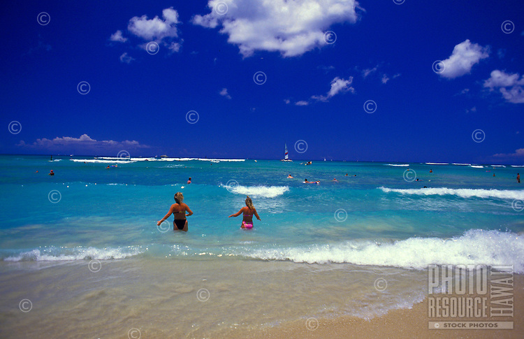 People running into the blue waters at Waikiki Beach