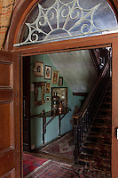 The door to the dining room opens onto a narrow staircase hall with a floor covered in a variety of rugs