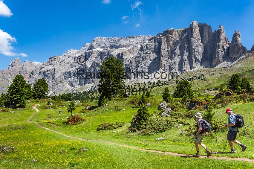 Italy, South Tyrol (Trentino - Alto Adige), Dolomites, near Selva di Val Gardena: hiking with Sella Group at Sella Pass Road   Italien, Suedtirol (Trentino - Alto Adige), oberhalb von Wolkenstein in Groeden: Wanderer vor der Sellagruppe an der Sella-Joch-Passstrasse