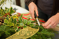 Sara Beth Kane of Mt. Airy cuts some holly to decorate her wreath at the Winter in the Wissahickon event hosted by the Friends of the Wissahickon on December 1. (Dave Tavani/for NewsWorks)