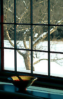 Carved painted handmade bowl sits on window sill looking out over New England winter, Vermont