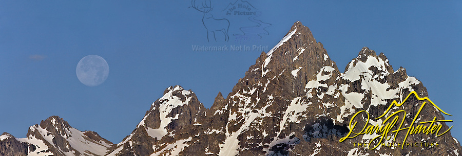 A full moon setting over the cathedral group of the Grand Tetons in Jackson Hole Wyoming.