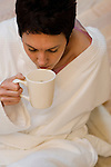 Mature woman drinking coffee in her bathrobe