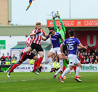 Exeter City's Christy Pym claims a high ball under pressure from Lincoln City's Elliott Whitehouse<br /> <br /> Photographer Chris Vaughan/CameraSport<br /> <br /> The EFL Sky Bet League Two Play Off First Leg - Lincoln City v Exeter City - Saturday 12th May 2018 - Sincil Bank - Lincoln<br /> <br /> World Copyright &copy; 2018 CameraSport. All rights reserved. 43 Linden Ave. Countesthorpe. Leicester. England. LE8 5PG - Tel: +44 (0) 116 277 4147 - admin@camerasport.com - www.camerasport.com