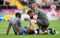 Lincoln City's John Akinde receives treatment for an injury from Lincoln City's strength and conditioning/sports massage Kieran Walker, centre, and Lincoln City sports science and medicine assistant Luke Treadwell<br /> <br /> Photographer Chris Vaughan/CameraSport<br /> <br /> Football Pre-Season Friendly - Lincoln City v Stoke City - Wednesday July 24th 2019 - Sincil Bank - Lincoln<br /> <br /> World Copyright © 2019 CameraSport. All rights reserved. 43 Linden Ave. Countesthorpe. Leicester. England. LE8 5PG - Tel: +44 (0) 116 277 4147 - admin@camerasport.com - www.camerasport.com