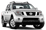 Low aggressive passenger side front three quarter view of 2010 Nissan Navara LE 4 door Pick-Up Truck .