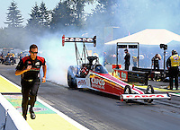 Aug. 3, 2014; Kent, WA, USA; A crew member runs beside NHRA top fuel dragster driver Steve Torrence doing a burnout during the Northwest Nationals at Pacific Raceways. Mandatory Credit: Mark J. Rebilas-