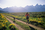 A young woman and her dog run on a dirt road in Grand Teton National Park, Jackson Hole, Wyoming.