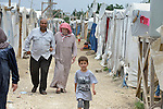 People walk in a settlement of Syrian refugees in Minyara, a village in the Akkar district of northern Lebanon. Lebanon hosts some 1.5 million refugees from Syria, yet allows no large camps to be established. So refugees have moved into poor neighborhoods or established small informal settlements in border areas. International Orthodox Christian Charities, a member of the ACT Alliance, provides support for families in this settlement.