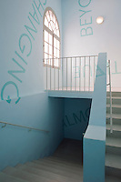Further modern graffiti lines the walls of a contemporary staircase in the 18th century building