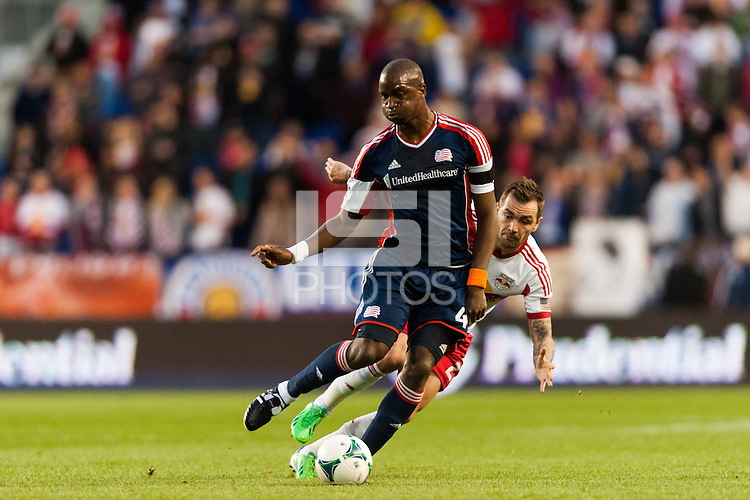 Kalifa Cisse (4) of the New England Revolution is marked by Brandon Barklage (25) of the New York Red Bulls. The New York Red Bulls defeated the New England Revolution 4-1 during a Major League Soccer (MLS) match at Red Bull Arena in Harrison, NJ, on March 20, 2013.