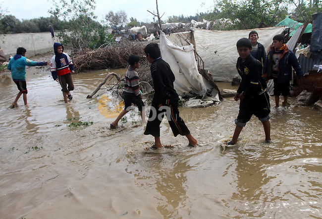 Palestinian Bedouin children walk through muddy waters after heavy rains which flooded the Al Moghraka area in the central Gaza Strip, 04 March 2012. Photo by Ashraf Amra