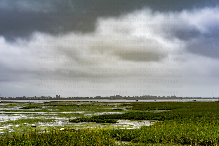 Scenic rural landscape view across an estruary with storm clouds and boats