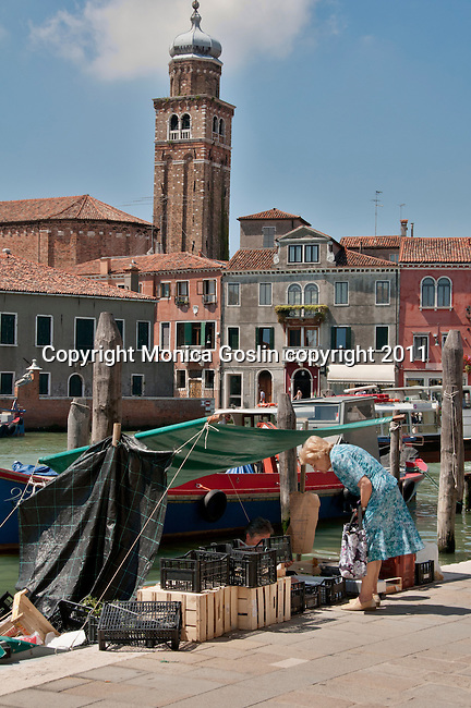 A woman buys fresh fruit and vegetables from a local food vendor, selling from a boat, at Murano Island outside of Venice, Italy