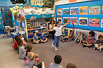 Berkeley CA  Preschool student performing in front of classmates in well-docorated classroom with aquatic theme.