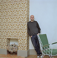 Designer and owner Jason Maclean leaning against a wall covered with Eley Kishimoto wallpaper next to an Ernest Race chair