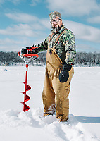 Brad Tschida drills an ice fishing hole at the 39th Annual International Eelpout Festival, at Leech Lake in Walker, Minnesota, February 23, 2018. Crowds that are more than 10 times the population of tiny Walker, Minn. (pop. 1,069) gather on Minnesota&rsquo;s third largest lake (112,000-acres), Leech Lake, for a festival named for one of the ugliest bottom-dwelling fish, the eelpout.<br /> <br /> Photo by Matt Nager