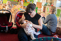 A mother breastfeeds her young baby at a drop-in breastfeeding support centre, while another mum plays with a toddler in the background.<br /> <br /> Hampshire, England, UK<br /> 05/03/2014<br /> <br /> &copy; Paul Carter / wdiip.co.uk