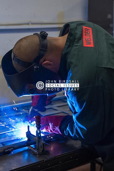 A prisoner welding in a prison workshop making prison beds in HMP Featherstone