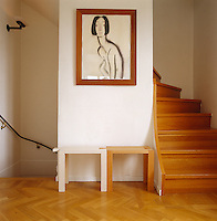 The landing has parquet flooring and a pair of interlocking wooden stools beneath a portrait