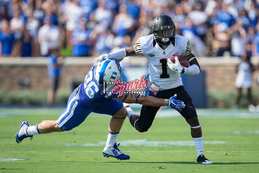 Tabari Hines (1) of the Wake Forest Demon Deacons stiff-arms Corbin McCarthy (26) of the Duke Blue Devils as he runs the ball during first half action at Wallace Wade Stadium on September 10, 2016 in Raleigh, North Carolina.  (Brian Westerholt/Sports On Film)