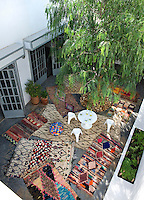 A view from above of the private courtyard terrace. The area is decked out with colourful rag rugs that give the space an informal air.