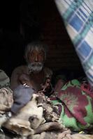 Old poor man hidding amongst old cloth in Bhaktapur, Layaku Nepal