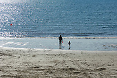 Cornwall, West Country, England. Sunny, April day. Polkerris, low tide, young woman with red bucket and child.