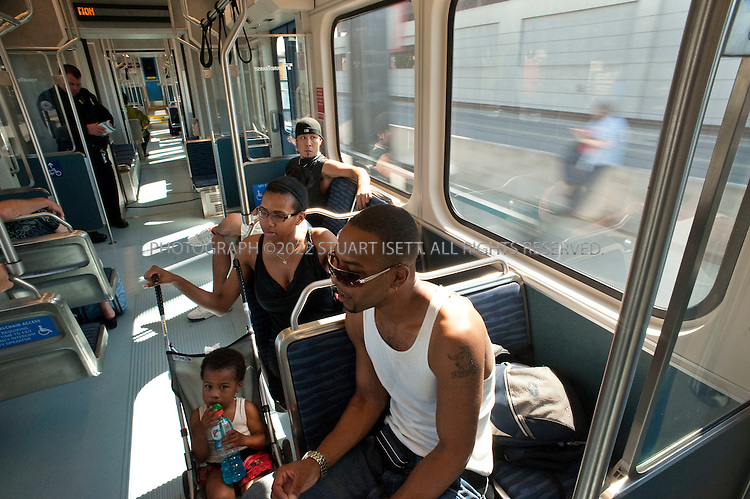 """7/28/2009--Seattle, WA, USA..Shauntel (left) and Stephon (right) Fosha, with their son Stacey, 2, take the Sound Transit Link train south out of Seattle to Beacon Hill where they live...The Sound Transit Link Light Rail opened in Seattle on July 20th 2009, after decades of planning and political wrangling. Construction of the city's new mass transit system took five years and cost $2.3 billion. By the end of the 2009 Sound Transit says light rail will reach Sea-Tac Airport; the train currently runs 14 miloes from the downtown Westlake station to Tukwila, south of Seattle, with extensions planned to run north and east out of the city.The first efforts to build modern rail transit in the Seattle area began about 50 years ago. A comprehensive plan was defeated by voters three times (1968, 1970, 1995), and then a shortened, """"starter"""" system was passed in 1996. ..©2009 Stuart Isett. All rights reserved."""
