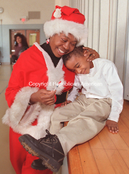 WATERBURY, CT 12/15/98 --1215JH01.tif--Wendy McDonald of Waterbury gives her son Eian, 4, a hug after they had helped her grandmother, Addie Booker, hand out Christmas gifts to kids at the Walsh Magnet School in Waterbury Tuesday.   About 600 kids at Walsh each got a toy and also a bag of goodies including popcorn, candy etc. Earlier in the day, Addie Booker made a similar visit to Driggs Schol, and also gave out gifts to around 600 kids. JOHN HARVEY staff photo STANDALONE PHOTO.