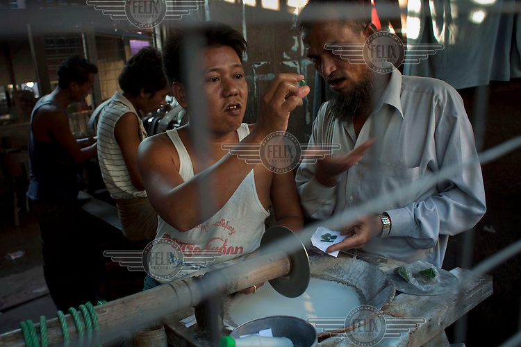 Jade traders examine a piece of jade at the Jade Market in Mandalay. Much of the Burmese junta's wealth comes from the trade in precious stones.
